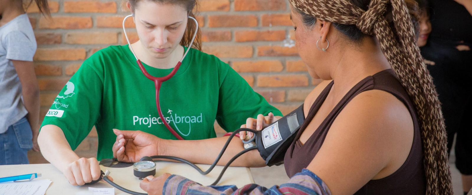 A medical volunteer in Mexico checks a patient's blood pressure during a healthcare outreach.
